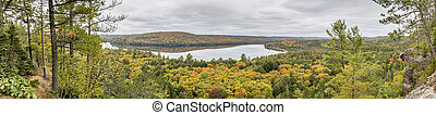 Panorama Looking Out Over a Lake Surrounded by Forest in Autumn