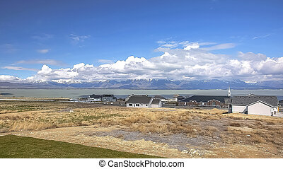 Panorama Neighborhood with view of lake and mountain under cloudy blue sky on a sunny day