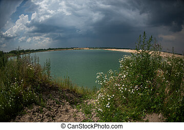 Panorama of a blue lake with a sandy shore. Lake view. Overcast sky.