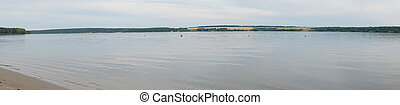 Panorama of a large river with a sandy Bank against a cloudy sky in evening