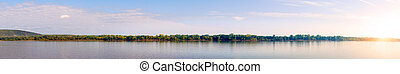 Panorama of a large river with a sandy Bank against cloudy sky in the evening