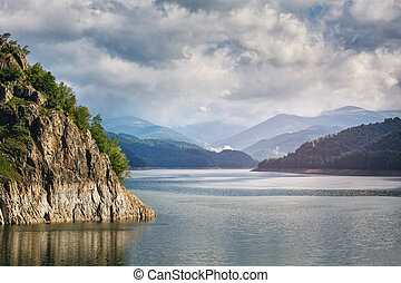 Panorama of a mountain lake Near the dam. Beautiful blue sky with clouds