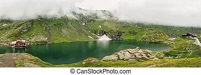 Panorama of a mountain lake. Typical alpine house on the mountain Balea lake.