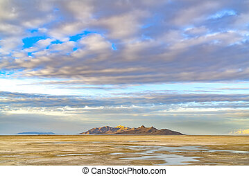 Panorama of a sandy lake shore under a blue sky filled with puffy clouds