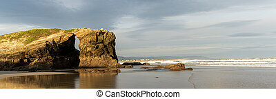 panorama of a sunrise at the Playa de las Catedrales Beach in Galicia in northern Spain