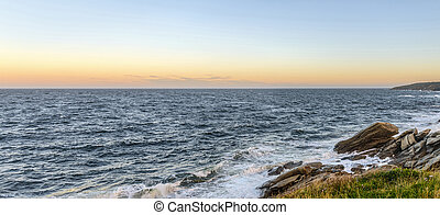 Panorama of an ocean shore at the crack of dawn