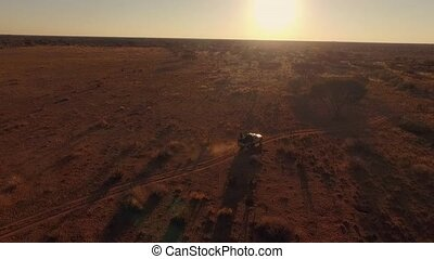 Panorama of an off-road car riding in the savannah of Namibia at sunset.