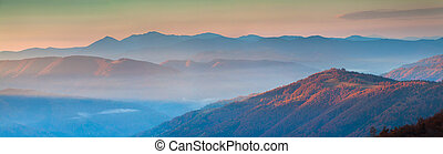 Panorama of autumn mountains in the morning mist