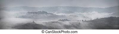 Panorama of autumn rain and fog on the mountain hills.