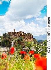 Panorama of Bagnoregio town, Lazio, Italy through poppy flower