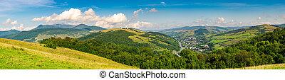 panorama of beautiful mountainous rural area. village down...