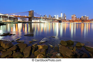 Panorama of Brooklyn Bridge, East River and Manhattan at sunset with lights and reflections. New York