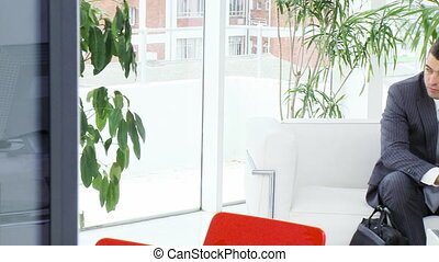 Panorama of businessmen sitting on sofa in a waiting room
