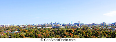 A panoramic view over the fall trees of Cambridge, MA, past the Soldier's Field stadium and the rest of Harvard University towards the skyscrapers of downtown Boston, MA.
