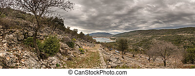 Panorama of city of Cres, marina and sea on a cloudy day in spring