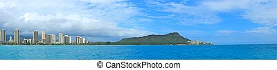 A panoramic shot of Diamond Head and Waikiki Beach with the towering buildings of Honolulu towering in the background