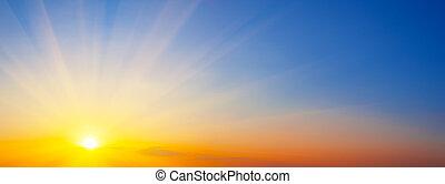 Panorama of dramatic sunset sky with sunbeams