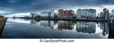 panorama of Dublin modern buildings with reflection in river Liffey , dark day