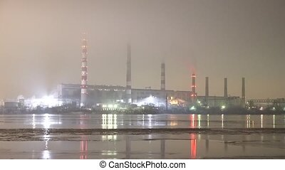 Panorama of electricity plant in fog near river by night