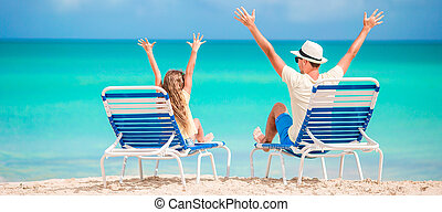 Panorama of family of dad and kid hands up on beach sitting on chaise-longue