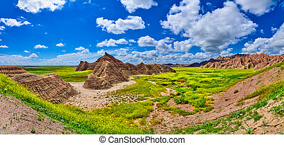 Panorama of formations with sunny skies at Badlands National Park.