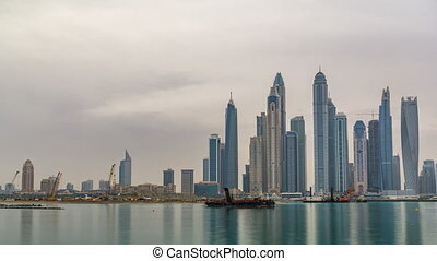 Panorama of modern skyscrapers in Dubai city at sunrise timelapse from the Palm Jumeirah Island.