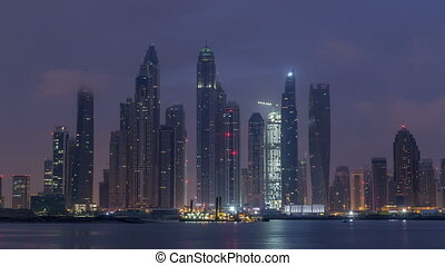 Panorama of modern skyscrapers in Dubai city night to day timelapse from the Palm Jumeirah Island.