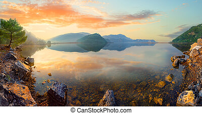 Panorama of mountain lake at sunset