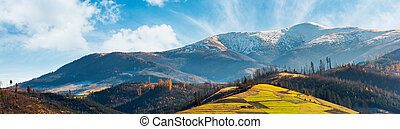 panorama of mountain ridge with snowy peak above the hill...