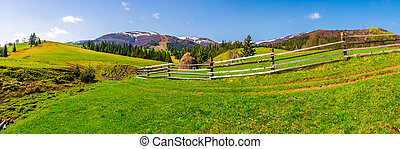 panorama of mountainous rural area. fence along the path on...