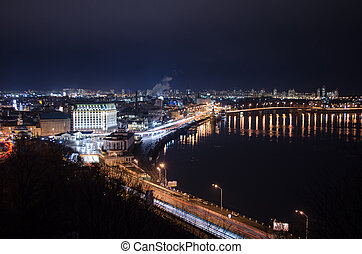 Panorama of night city landscape with river and bridge. Reflection of glowing lanterns in water.