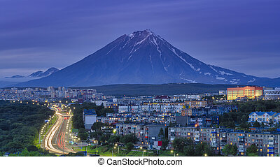 Panorama of night city of Petropavlovsk-Kamchatsky on background of volcano, urban development at twilight, backlit city road with car lights