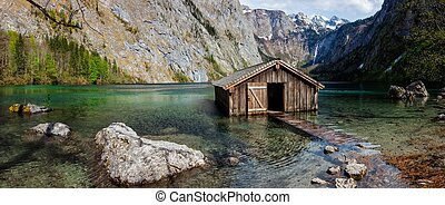 Panorama of Obersee mountain lake with boat dock hangar in Alps. Bavaria, Germany