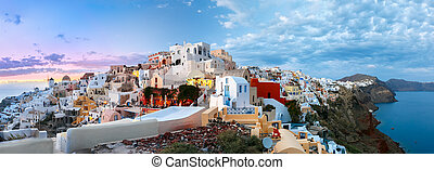 Picturesque panorama, Old Town of Oia or Ia on the island Santorini, white houses, windmills and church with blue domes at sunset, Greece
