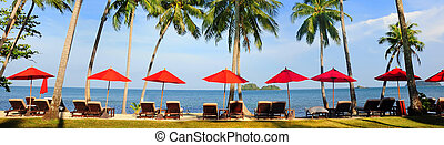 Panorama of perfect tropical beach with red umbrellas