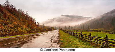 Panorama of road in mountains. Cloudy rainy misty autumn day panorama