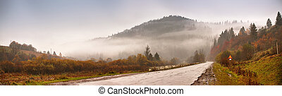 Panorama of road in mountains. Mountain hills in clouds of fog