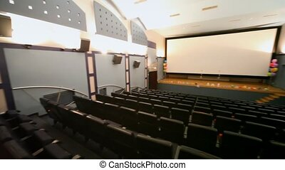 Panorama of small almost empty light cinema hall decorated...