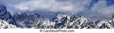 Panorama of snowy mountains in haze at sunny winter day