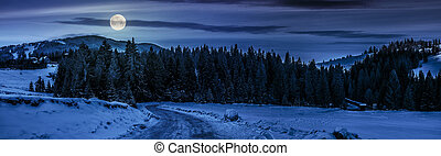 panorama of snowy road through spruce forest in mountains at...