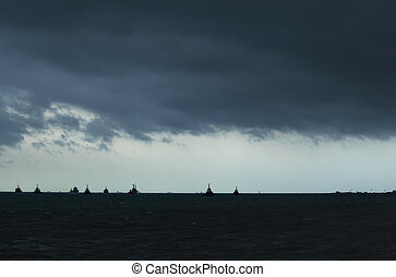 Panorama of stormy black sea with ships on the horizon