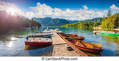 Panorama of summer sunny morning on the Bohinj Lake with boats, Triglav National Park, Julian Alps, Slovenia