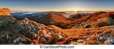 Panorama of sunset in a Carpathian mountain valley with wonderful gold light on a hills