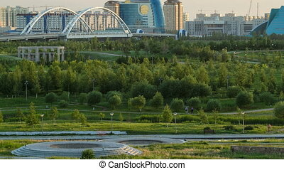 Panorama of the Astana city before sunset timelapse with bridge and buildings. View over the park