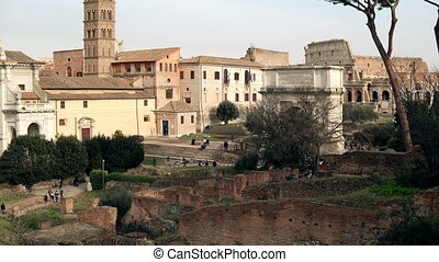 Panorama of the Rome, Italy city view with its ruins, columns, palaces and an impressive Arch of Titus and Colosseum.
