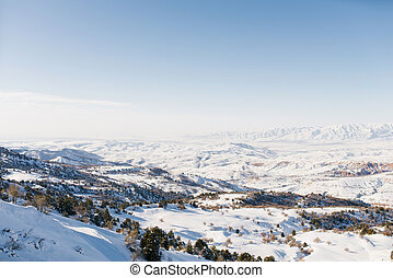 Panorama of the Tien Shan mountains covered with snow in Sunny weather. Winter landscape in the mountains of the Beldersay ski resort