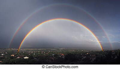 Panorama of the two large raibows over the the city after the rain view from mountain