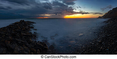 Panorama of three frames a general view of the rocky shore of the Black Sea coast after sunset, Anapa, Russia