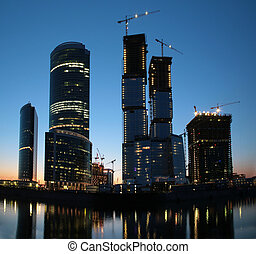 Panorama of under construction skyscraper on sunset