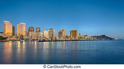 Panorama of the nightime skyline of Honolulu and Waikiki from Ala Moana park as the sun sets and illuminates the facades of the hotels and apartments